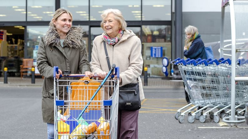 A woman and her mother walking to their car pushing a shopping trolley