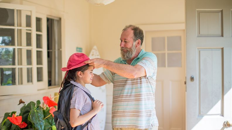 Man in his late fifties helping his granddaughter put on her sun hat.