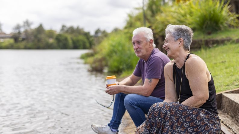 Mature aged caucasian couple sitting by a river.
