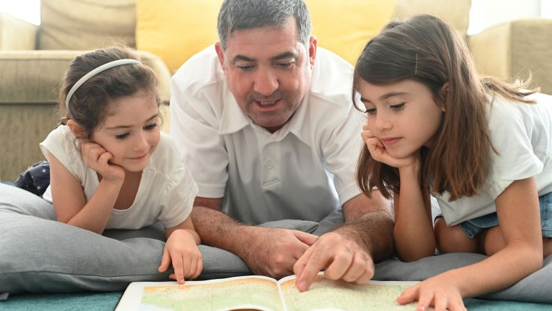 Father and his two daughters laying on the floor together reading a book