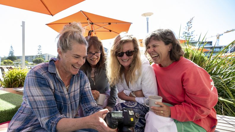 A group of causacian women sitting outdoors at a restaurant laughing and looking at images on a camera.