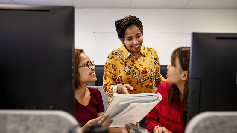 An east-asian woman stands between two other women who are sitting at computers in a classroom setting. She is answering a question they have asked her.